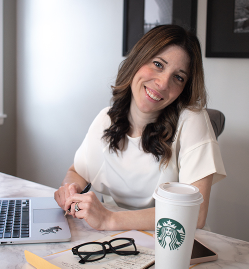 Biography image of Liz Nunziato, Freelance Graphic Designer in Buffalo, NY. Woman sitting at table with apple laptop, coffee, paperwork, phone, and glasses